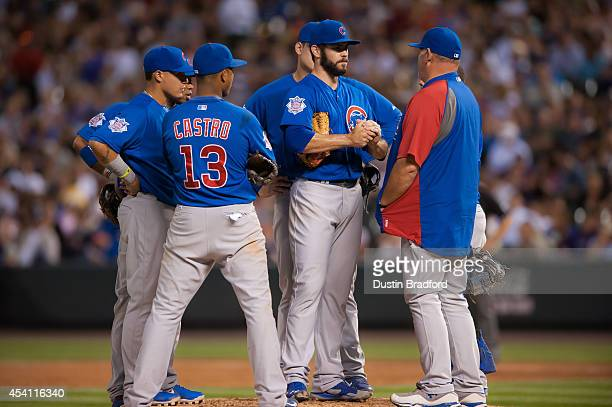 Jake Arrieta of the Chicago Cubs has a word with pitching coach Chris Bosio during a game against the Colorado Rockies at Coors Field on August 6...