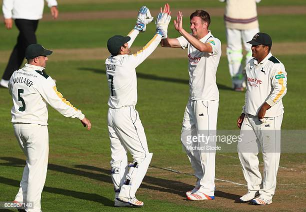 Jake Ball of Nottinghamshire celebrates taking the wicket of Peter Trego with captain Chris Read during day one of the Specsavers County Championship...