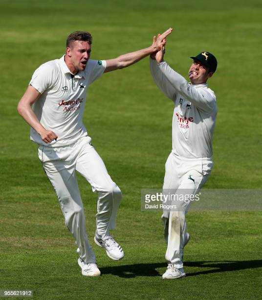 Jake Ball of Nottinghamshire celebrates with team mate Jake Libby after taking the wicket of Kyle Abbott during day four of the Specsavers County...