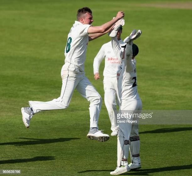 Jake Ball of Nottinghamshire celebrates with team mate Tom Moores after taking the match winning wicket of Hashim Amla during day four of the...