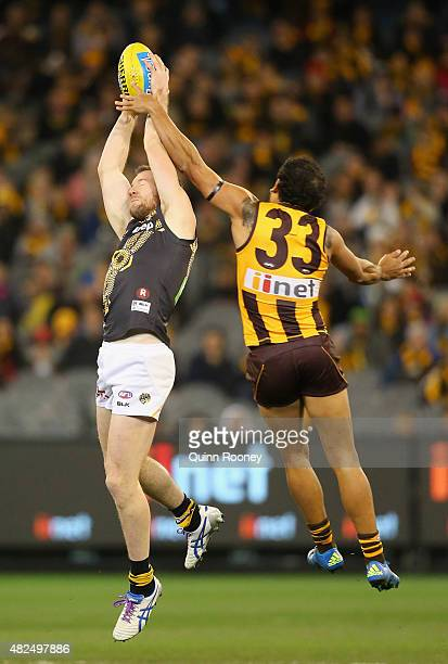 Jake Batchelor of the Tigers marks infront of Cyril Rioli of the Hawks during the round 18 AFL match between the Hawthorn Hawks and the Richmond...