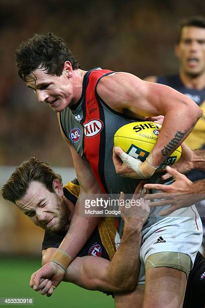 Jake Batchelor of the Tigers tackles Jake Carlisle of the Bombers during the round 20 AFL match between the Richmond Tigers and the Essendon Bombers...