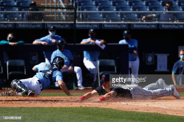 Jake Bauers of the Cleveland Indians slides into home plate to score a run against the Seattle Mariners during the first inning of the MLB spring...