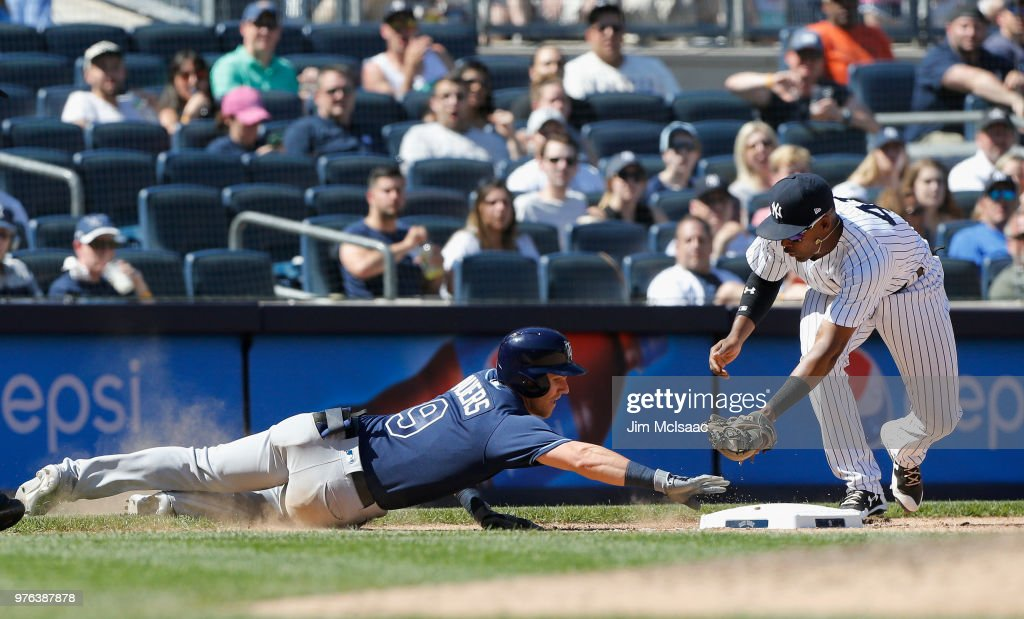 Jake Bauers #9 of the Tampa Bay Rays dives safely back to third base ahead of the tag from Miguel Andujar #41 of the New York Yankees for a triple in the ninth inning at Yankee Stadium on June 16, 2018 in the Bronx borough of New York City.