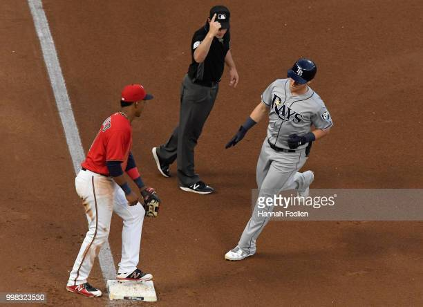 Jake Bauers of the Tampa Bay Rays rounds the bases as Jorge Polanco of the Minnesota Twins looks on at third base and umpire Quinn Wolcott signals a...