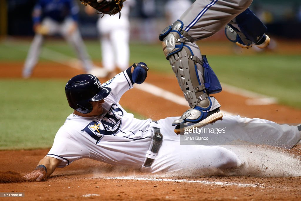 Jake Bauers #9 of the Tampa Bay Rays slides home as catcher Russell Martin #55 of the Toronto Blue Jays leaps over him to score off of a fielder's choice by Joey Wendle during the seventh inning of a game on June 11, 2018 at Tropicana Field in St. Petersburg, Florida.