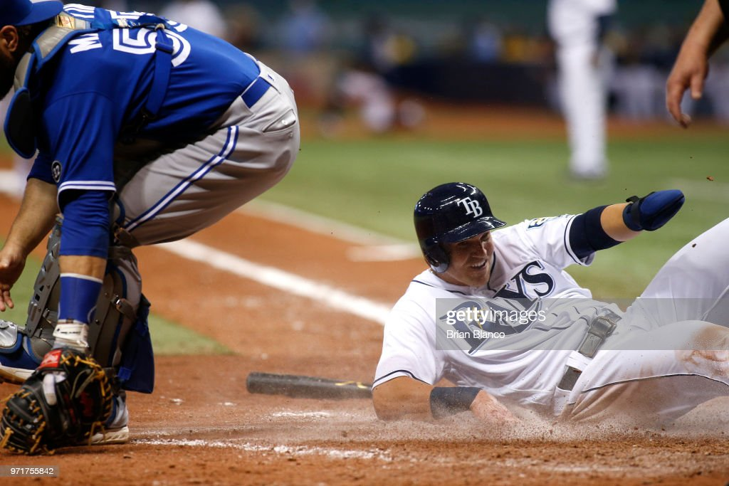 Jake Bauers #9 of the Tampa Bay Rays slides home avoiding catcher Russell Martin #55 of the Toronto Blue Jays to score off of a fielder's choice by Joey Wendle during the seventh inning of a game on June 11, 2018 at Tropicana Field in St. Petersburg, Florida.