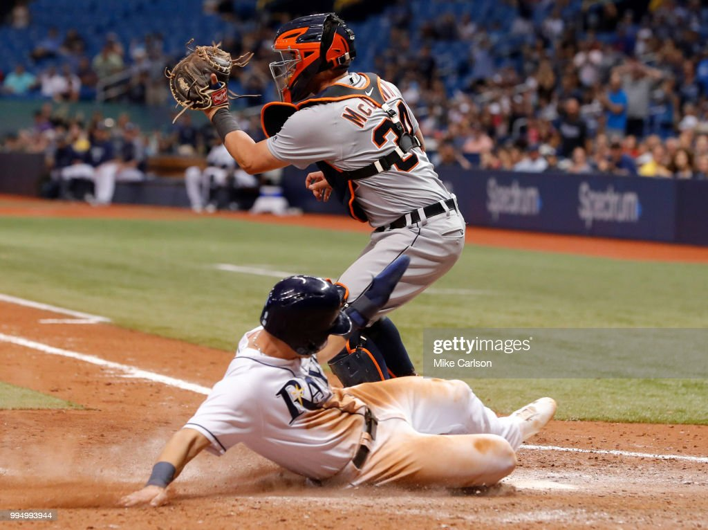 Jake Bauers #9 of the Tampa Bay Rays slides in to score behind catcher James McCann #34 of the Detroit Tigers in the eighth inning of a baseball game at Tropicana Field on July 9, 2018 in St. Petersburg, Florida.