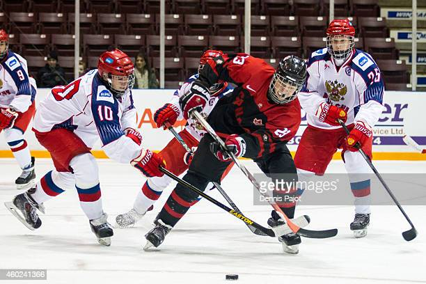 Jake Bean of Canada Black moves the puck against Nikita Makeyev and Mikhail Mesheryakov of Russia during the World Under17 Hockey Challenge on...