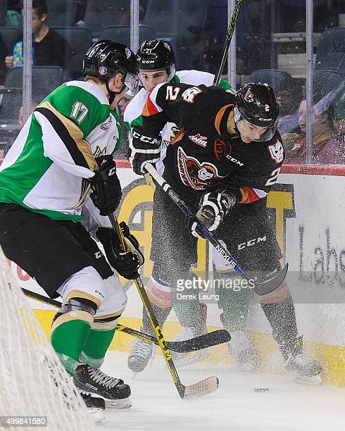 Jake Bean of the Calgary Hitmen battles for the puck against Dylan Williamson of the Prince Albert Raiders during a WHL game at Scotiabank Saddledome...