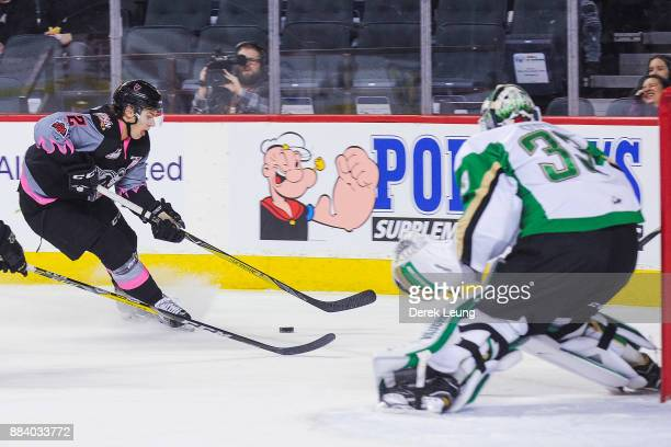 Jake Bean of the Calgary Hitmen carries the puck in front of the net of Ian Scott of the Prince Albert Raiders during a WHL game at the Scotiabank...