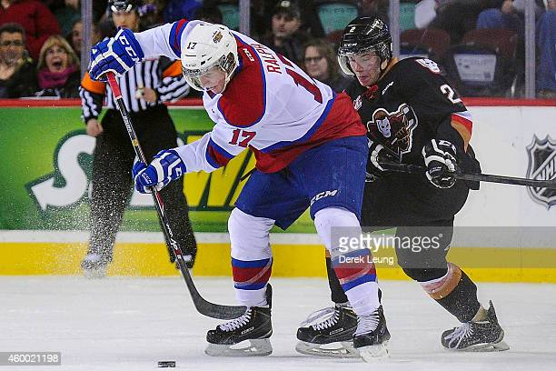 Jake Bean of the Calgary Hitmen chases Brandon Ralph of the Edmonton Oil Kings during a WHL game at Scotiabank Saddledome on December 5 2014 in...