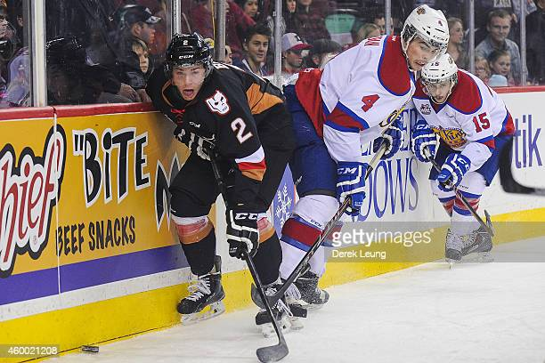 Jake Bean of the Calgary Hitmen fights for the puck against Blake Orban of the Edmonton Oil Kings during a WHL game at Scotiabank Saddledome on...