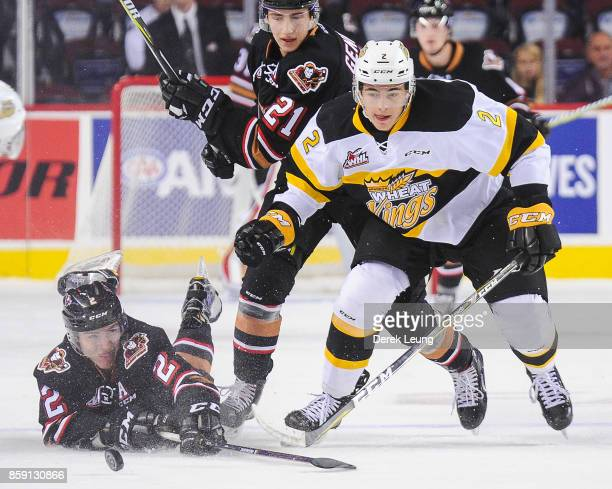 Jake Bean of the Calgary Hitmen loses the puck to Braden Schneider of the Brandon Wheat Kings during a WHL game at the Scotiabank Saddledome on...