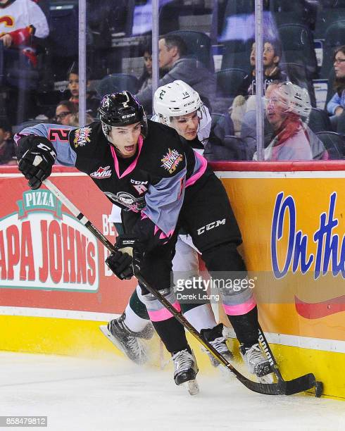 Jake Bean of the Calgary Hitmen skates with the puck past Riley Sutter of the Everett Silvertips during a WHL game at the Scotiabank Saddledome on...