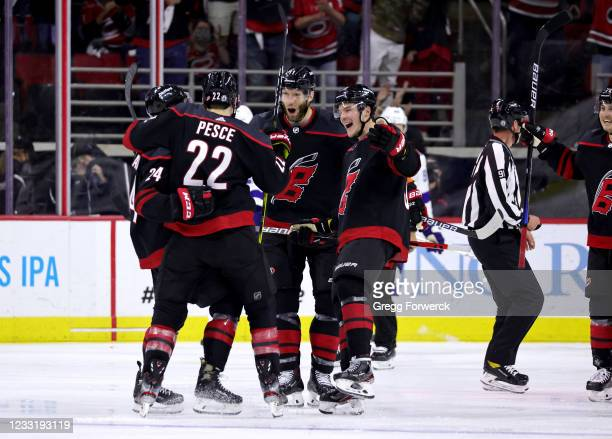 Jake Bean of the Carolina Hurricanes celebrates his third period goal with teammates Jordan Staal, Andrei Svechnikov, and Brett Pesce in Game One of...