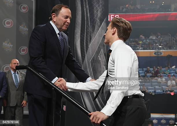 Jake Bean shakes hands with NHL Commissioner Gary Bettman after being selected 13th overall by the Carolina Hurricanes during round one of the 2016...
