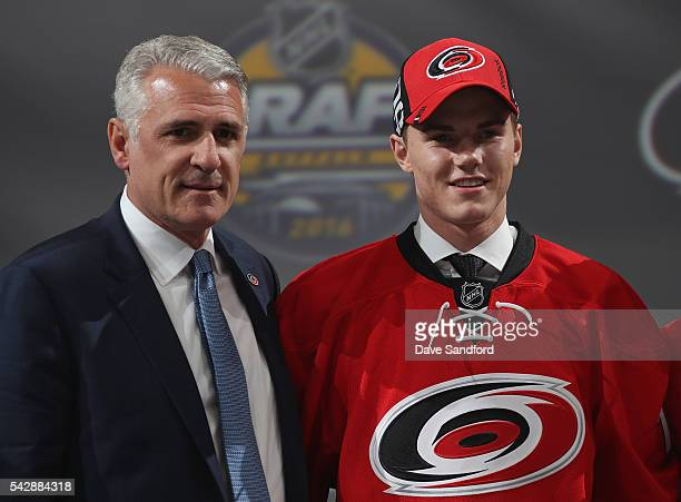 Jake Bean stands onstage with general manager Ron Francis after being selected 13th overall by the Carolina Hurricanes during round one of the 2016...