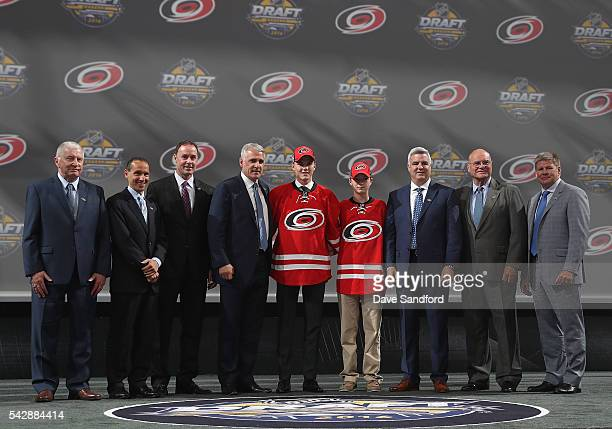 Jake Bean stands onstage with team personnel after being selected 13th overall by the Carolina Hurricanes during round one of the 2016 NHL Draft at...