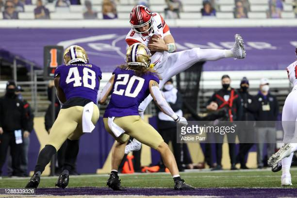 Jake Bentley of the Utah Utes jumps into the end zone to score a one yard touchdown against the Washington Huskies in the first quarter to take a 7-0...