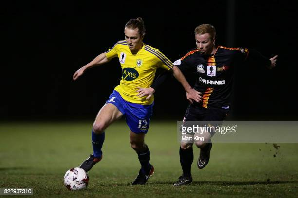 Jake Bradshaw of the Bankstown Berries is challenged by Tim Henderson of the MetroStars during the FFA Cup round of 32 match between Bankstown...