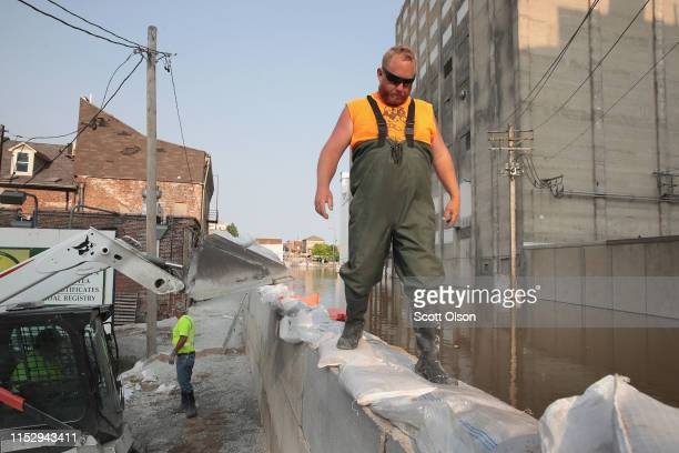Jake Buehlman helps to construct a temporary floodwall along Highway 100 to keep floodwater from the Mississippi River out of the historic downtown...
