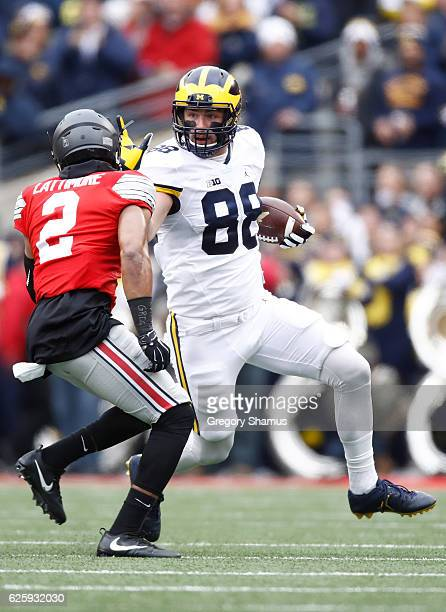 Jake Butt of the Michigan Wolverines carries the ball after catching a pass during the first quarter against the Ohio State Buckeyes at Ohio Stadium...