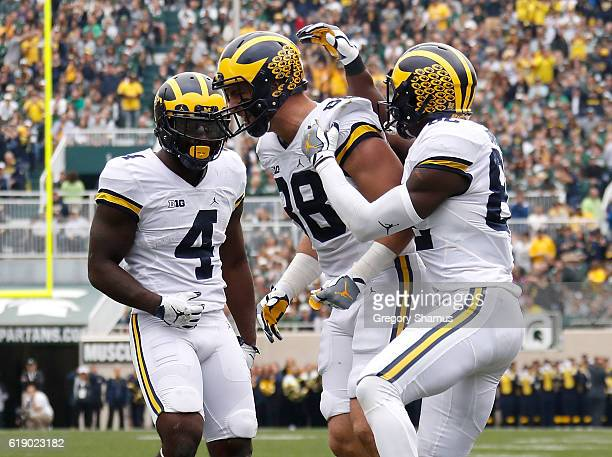 Jake Butt of the Michigan Wolverines celebrates a second quarter catch with De'Veon Smith and Amara Darboh while playing the Michigan State Spartans...