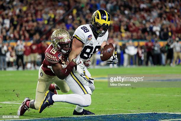 Jake Butt of the Michigan Wolverines completes a pass against the defense of AJ Westbrook of the Florida State Seminoles in the first half during the...
