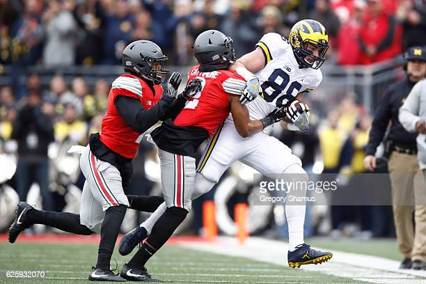 Jake Butt of the Michigan Wolverines is tackled by Marshon Lattimore of the Ohio State Buckeyes after catching a pass during the first quarter of...