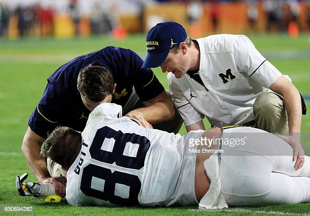Jake Butt of the Michigan Wolverines receives medical attention in the first half against the Florida State Seminoles during the Capitol One Orange...