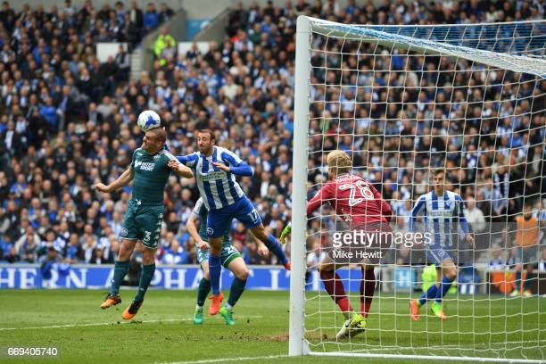 Jake Buxton of Wigan heads clear under pressure from Glenn Murray of Brighton during the Sky Bet Championship match between Brighton Hove Albion and...