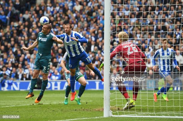 Jake Buxton of Wigan wins a header with Glenn Murray of Brighton and Hove Albion during the Sky Bet Championship match between Brighton and Hove...