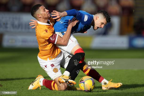 Jake Carroll of Motherwell tackles Ianis Hagi of Rangers during the Ladbrokes Scottish Premiership match between Motherwell and Rangers at Fir Park...