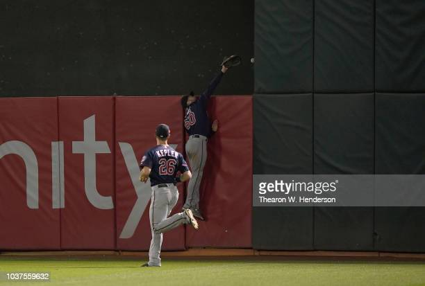 Jake Cave of the Minnesota Twins leaps at the wall and watches the ballgo over for a walkoff solo home run off the bat of Khris Davis of the Oakland...