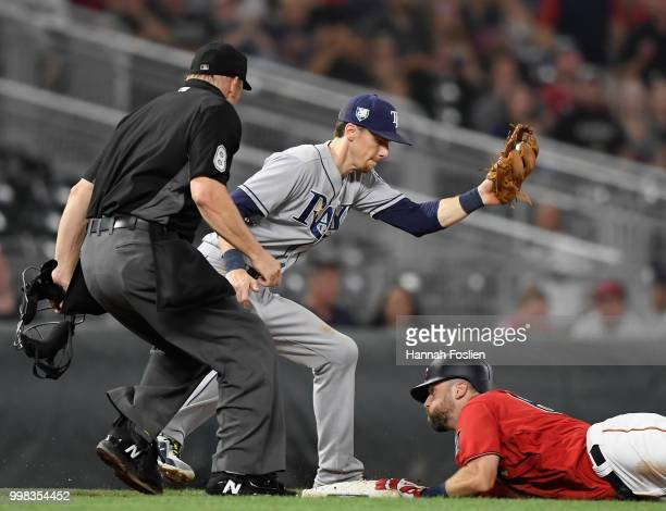Jake Cave of the Minnesota Twins slides into third base safely with a triple as Matt Duffy of the Tampa Bay Rays fields the ball and home plate...