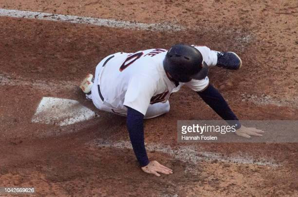 Jake Cave of the Minnesota Twins slides safely into home plate to score a run against the Chicago White Sox during the sixth inning in game one of a...