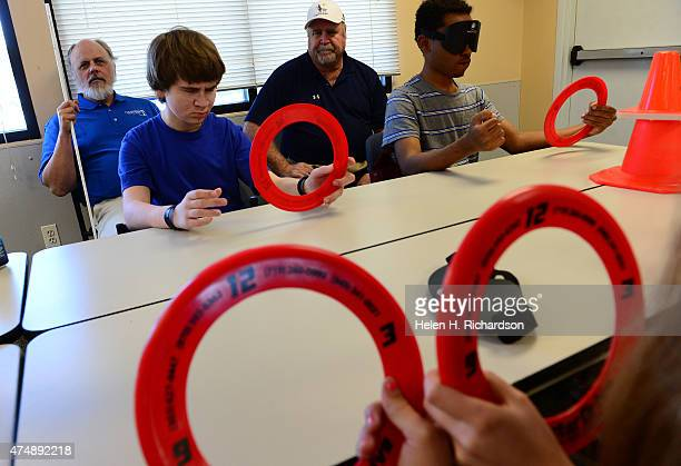 Jake Cohen in blue practices using a steering wheel with a plastic frisbee with his father Dave in white hat in background watches during an...