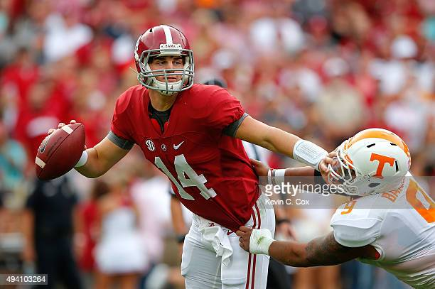 Jake Coker of the Alabama Crimson Tide breaks a tackle as he stiff arms Derek Barnett of the Tennessee Volunteers at BryantDenny Stadium on October...