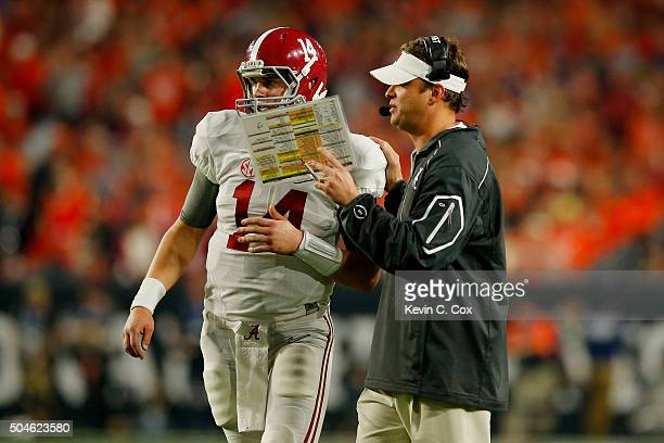 Jake Coker of the Alabama Crimson Tide talks with offensive coordinator Lane Kiffin in the first half while taking on the Clemson Tigers during the...