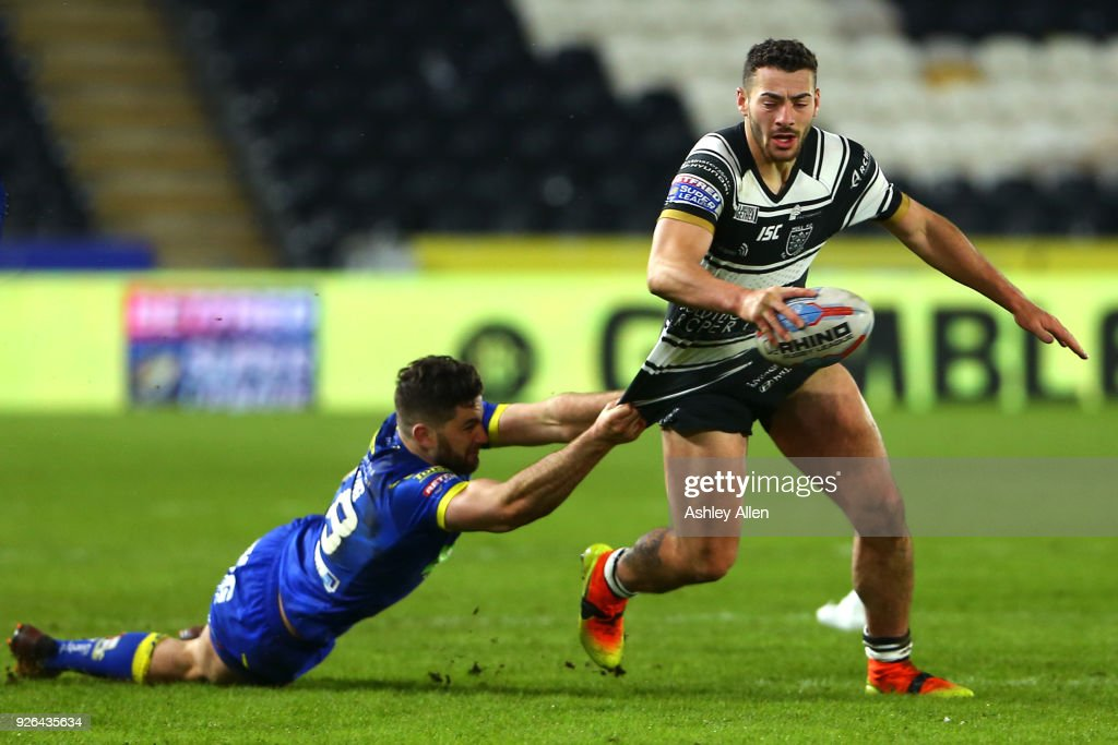 Jake Connor (R) of Hull FC avoids a tackle from Toby King (L) of Warrington Wolves during the BetFred Super League match between Hull FC and Warrington Wolves at KCOM Stadium on March 2, 2018 in Hull, England.