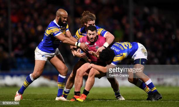 Jake Connor of Hull FC is tackled by Jamie JonesBuchanan Anthony Mullally and Josh Walters of Leeds during the Betfred Super League match between...