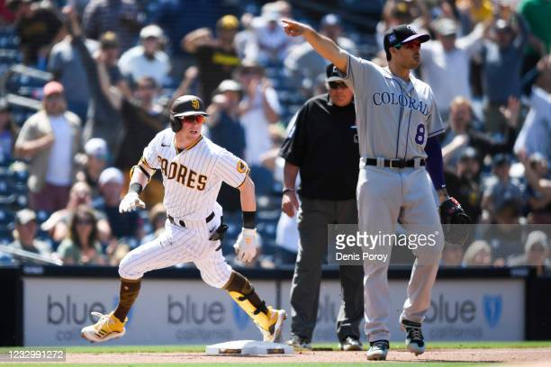Jake Cronenworth of the San Diego Padres rounds third base next to Josh Fuentes of the Colorado Rockies on his way to scoring on an inside-the-park...