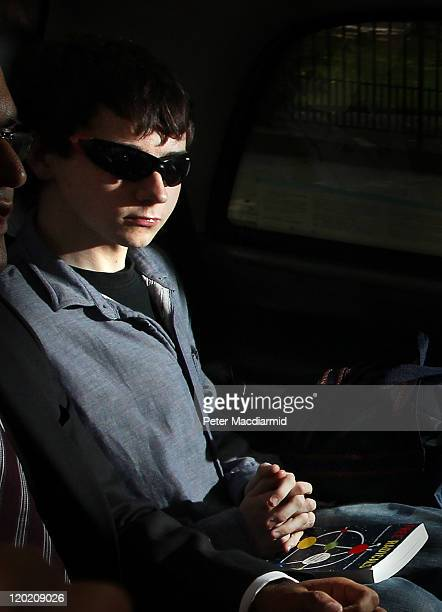 Jake Davis sits in a taxi with the book 'Free Radicals: The Secret Anarchy of Science' by Michael Brooks as he leaves Westminster Magistrates Court...