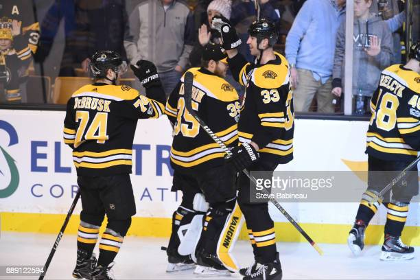 Jake DeBrusk and Zdeno Chara of the Boston Bruins celebrate a win against the New York Islanders at the TD Garden on December 9 2017 in Boston...