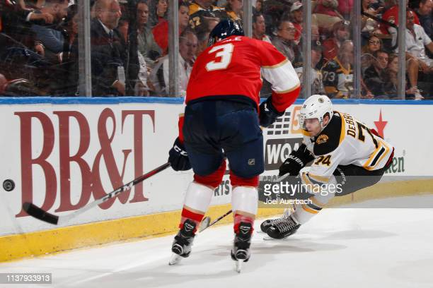 Jake DeBrusk of the Boston Bruins and Keith Yandle of the Florida Panthers battle for possession of the puck during second period action at the BBT...
