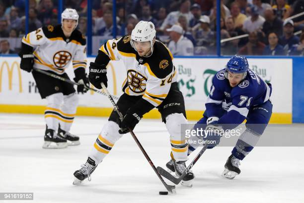 Jake DeBrusk of the Boston Bruins avoids a check from Anthony Cirelli of the Tampa Bay Lightning during the third period of the game at the Amalie...