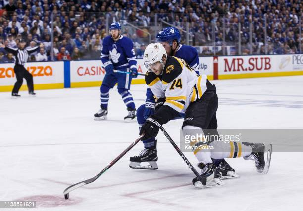 Jake DeBrusk of the Boston Bruins battles for the puck against Morgan Rielly of the Toronto Maple Leafs during the third period during Game Six of...
