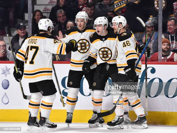 Jake DeBrusk of the Boston Bruins celebrates his first period goal with teammates Torey Krug John Moore and David Krejci against the Montreal...