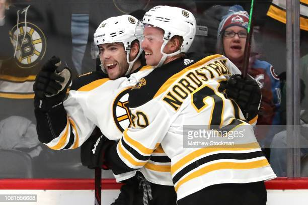 Jake DeBrusk of the Boston Bruins celebrates his goal with Joakim Nordstrom against the Colorado Avalanche in the first period at the Pepsi Center on...